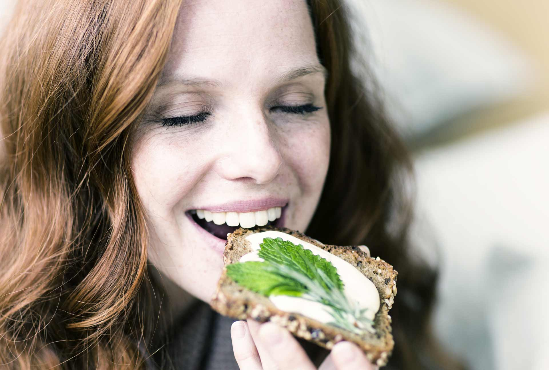 ragazza vegana che mangia pane con olio spalmabile reolì extravergine